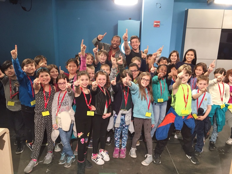 Azia poses with students from PS40 during their visit to Channel One News